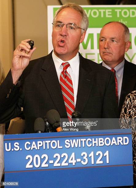 S Rep John Shimkus holds up a piece of coal as he speaks and Rep Pete Hoekstra listens during a news conference to call on Speaker of the House Rep...