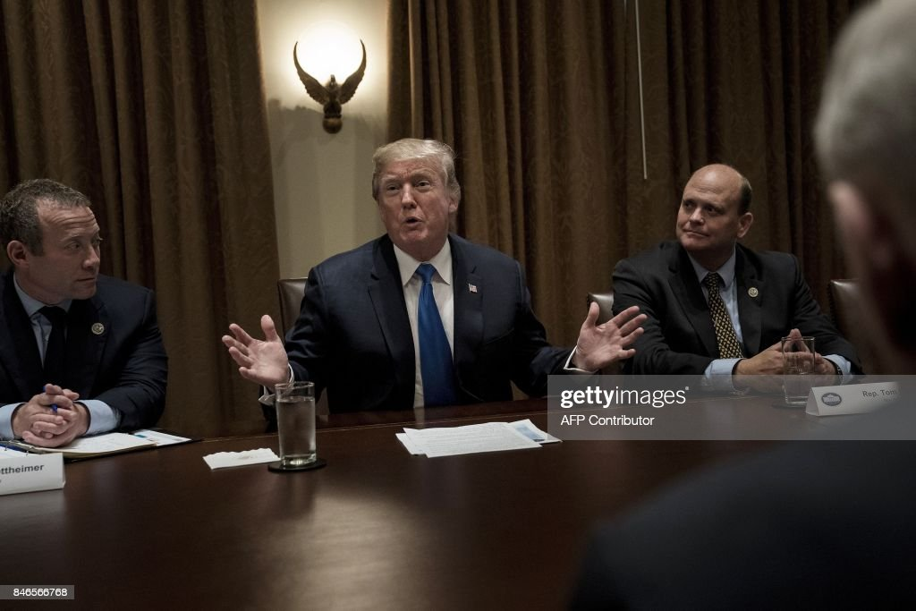 Rep. Josh Gottheimer (Democrat from New Jersey -L), Rep. Tom Reed (Republican from New York-2nd R) and White House Chief of Staff John Kelly (R) listen on while US President Donald Trump addresses a meeting with lawmakers in the Cabinet Room of the White House on September 13, 2017 in Washington, DC. / AFP PHOTO / Brendan Smialowski