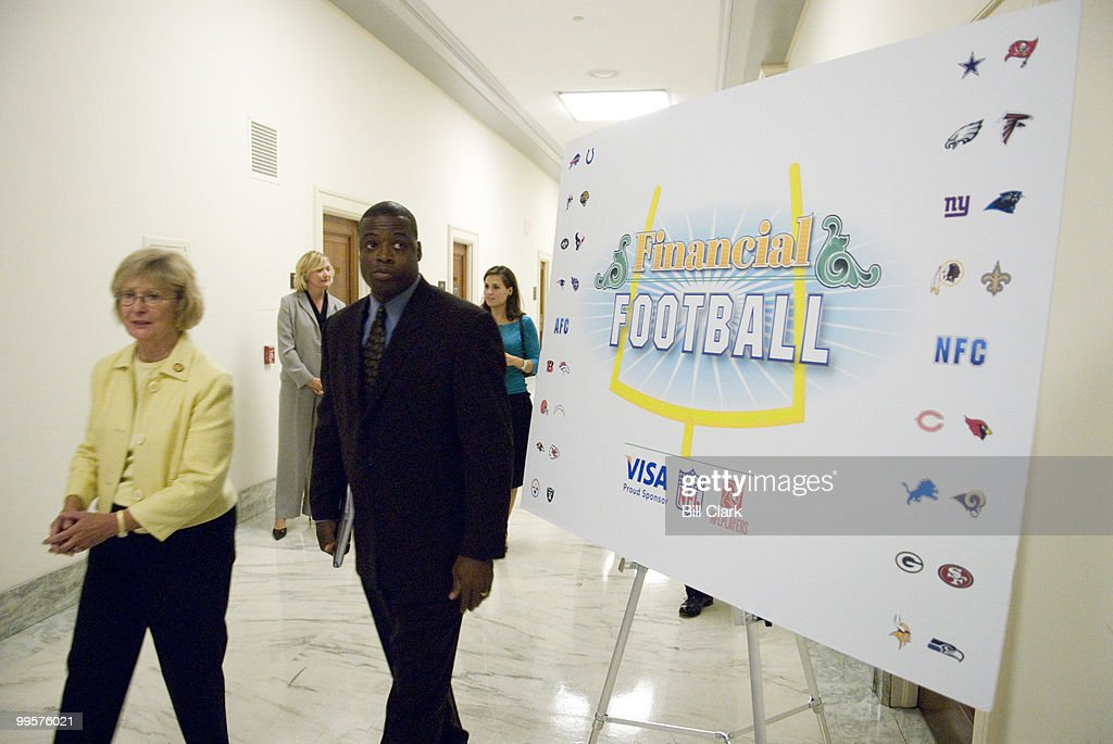 Rep. Judy Biggert, R-Ill., arrives with former Washington Redskins All-Pro player Darrell Green for the kick-off event for the 2006 season of financial interactive football game on Tuesday, Sept. 5, 2006 in the Rayburn Building. Former Redskins plater Brian Mitchell also attended. The game can be played online, and combines the rules of the NFL with financial education questions. Players gain yards and score as they answer financial questions correctly. The game will play a central role in the upcoming seventeen city Visa campaign to promote financial literacy in high schools across the country. Visa partnered with the NFL and the NFL Players Association for this project.