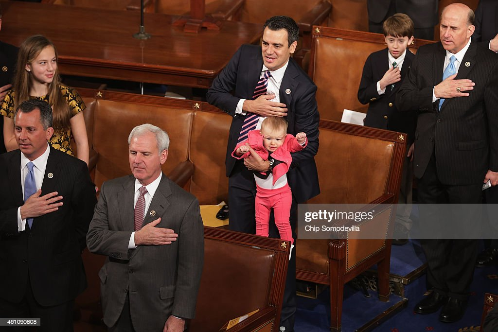 Rep. Kevin Yoder (R-KS) (C) holds his daughter Caroline Lucille Yoder while reciting the Pledge of Allegiance during the opening session of the 114th Congress inside the House of Representatives chamber at the U.S. Capitol January 6, 2015 in Washington, DC. Republicans now control both the House and Senate.