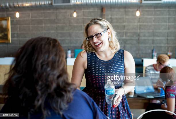 Rep Kyrsten Sinema DAriz shakes hands with a constituent at Giant Coffee in Phoenix on Thursday Aug 8 2014