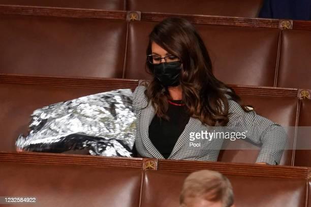 Rep. Lauren Boebert holds a lightweight blanket as U.S. President Joe Biden addresses a joint session of Congress in the House chamber of the U.S....