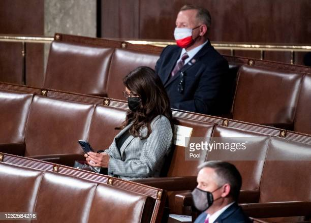 Rep. Lauren Boebert, R-Colo., checks her phone as President Joe Biden delivers his address to the joint session of Congress in the House chamber of...