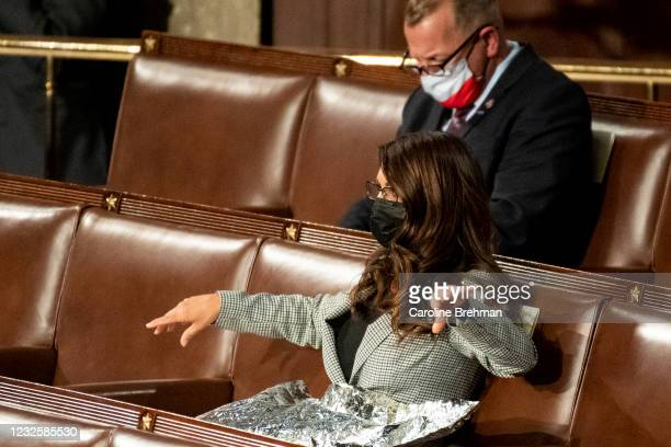 Rep. Lauren Boebert, R-Colo., spreads out what appears to be a foil space blanket as President Joe Biden delivers his address to the joint session of...