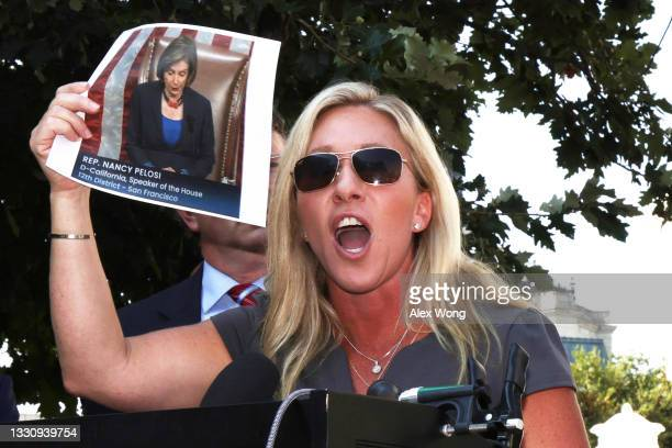 Rep. Marjorie Taylor Greene holds up a picture of Speaker of the House Rep. Nancy Pelosi as she speaks during a news conference outside U.S. Supreme...