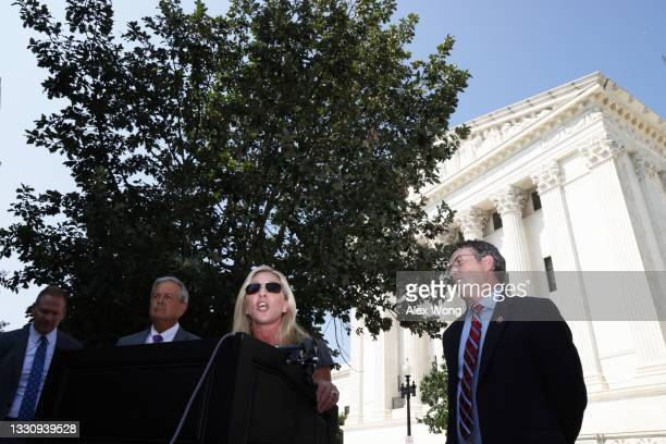 Rep. Marjorie Taylor Greene speaks as Rep. Ralph Norman and Rep. Thomas Massie listen during a news conference outside U.S. Supreme Court on July 27,...