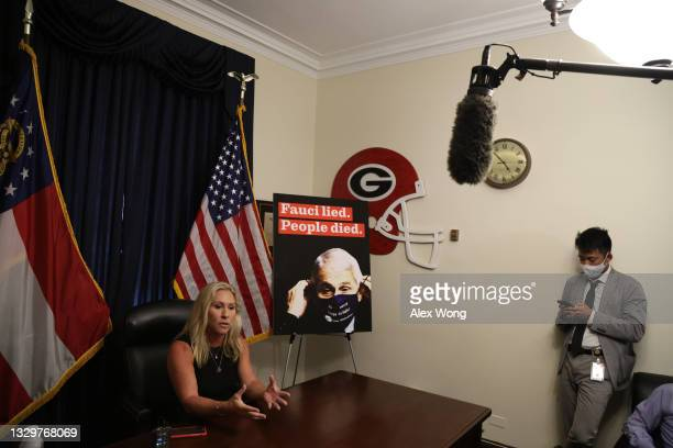 Rep. Marjorie Taylor Greene speaks during a news conference in her office at Longworth House Office Building with a poster of director of the...