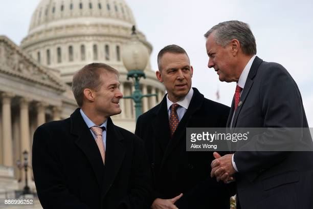 S Rep Mark Meadows talks to Rep Jim Jordan and Rep Scott Perry during a news conference in front of the Capitol December 6 2017 in Washington DC Rep...