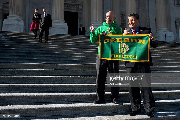 Rep Mark Takai DHawaii left and Rep Peter DeFazio DOre pose for photos with an Oregon Ducks banner on the steps of the Capitol on Friday Jan 9 2015...