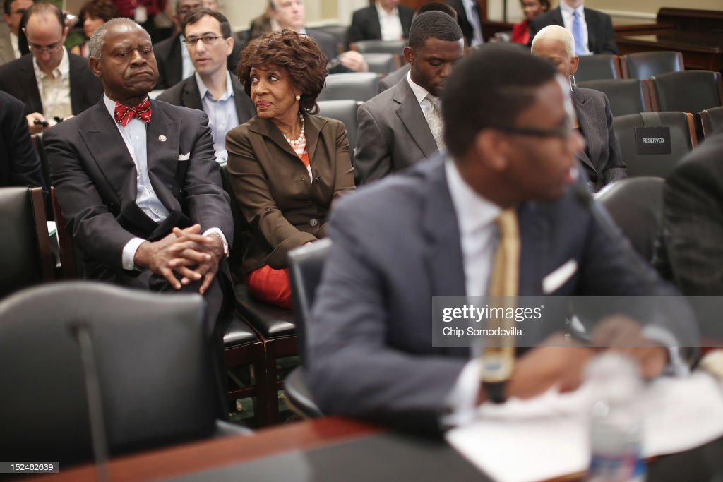 Rep. Maxine Waters (D-CA) (C), her husband Sidney Williams (L) and her grandson and Chief of Staff Mikael Moore (R) wait for the start of a rare open House Committee on Ethics hearing in the Longworth House Office Building on Capitol Hill September 21, 2012 in Washington, DC. A long-running investigation found that Waters did not commit an ethics violaiton when her office in late 2008 set up a meeting with top Treasury Department officials on behalf of a bank Williams owned stock in, at a time when the bank faced possible collapse because of the financial crisis. However, Moore was issued a letter of reproval for three ethics violations for helping the bank.