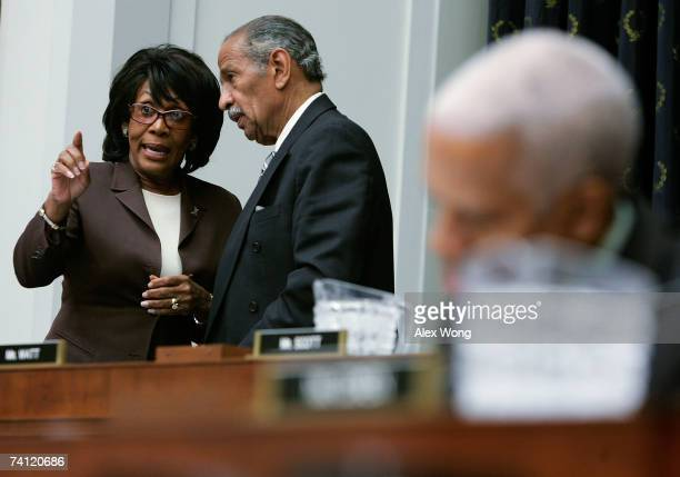S Rep Maxine Waters talks with committee Chairman Rep John Conyers after her turn of asking questions during a House Judiciary Committee hearing with...