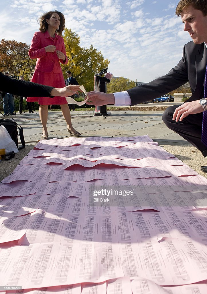 Rep. Michele Bachmann, R-Minn., looks over the 'pink slips' backdrop as she arrives at the House Triangle on Tuesday, Nov. 17, 2009, for a news conference on 'pink slips' for members of Congress who vote for government controlled health care