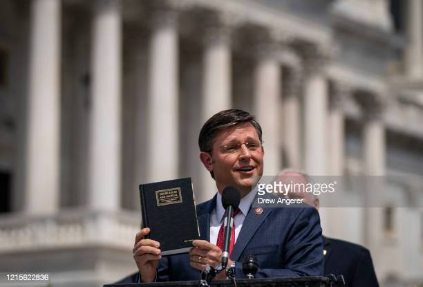 Rep. Mike Johnson holds up a House Rules and Manual book during a news conference outside the U.S. Capitol, May 27, 2020 in Washington, DC. Calling...