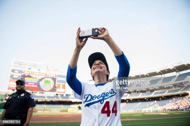 Rep Nanette Barragan DCalif takes photos before the start of the annual Congressional Baseball Game at Nationals Park in Washington on Thursday June...