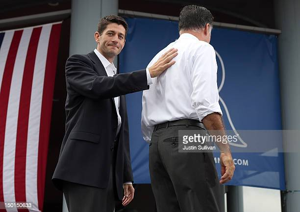 S Rep Paul Ryan touches the back of Republican presidential candidate former Massachusetts Gov Mitt Romney as he was announced as his vice...