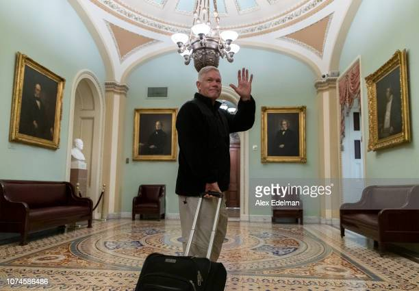 Rep Pete Sessions waves to reporters as he departs the US Capitol on December 22 2018 in Washington DC Democrats refused to agree with President...