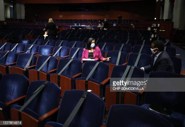 Rep. Pramila Jayapal and Rep. Joseph Neguse practice social distancing while waiting for the start of a hearing where US Attorney General William...