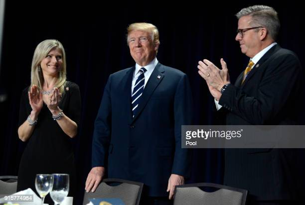 Rep Randy Hultgren and his wife Christy clap for President Donald Trump at the National Prayer Breakfast on February 8 2018 in Washington DC...