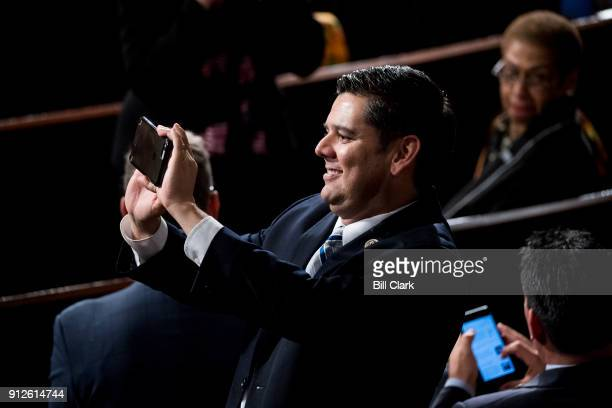 Rep Raul Ruiz DCalif takes a photo with his phone before President Donald Trump's State of the Union Address to the joint session of Congress in the...