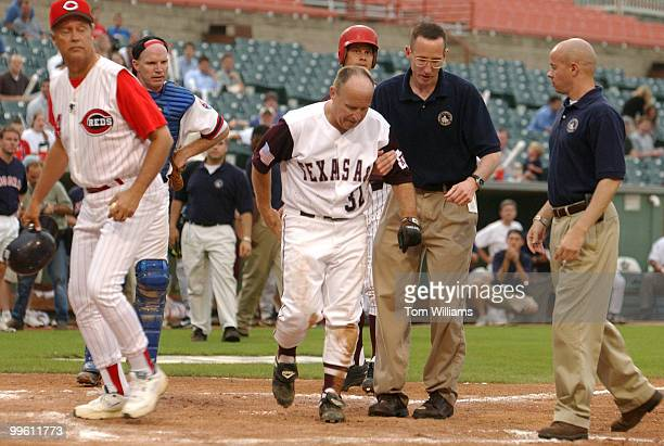 Rep Rep Kevin Brady RTexas is escorted of the field after a collision at home plate during the Congressional Baseball game in which the Republicans...