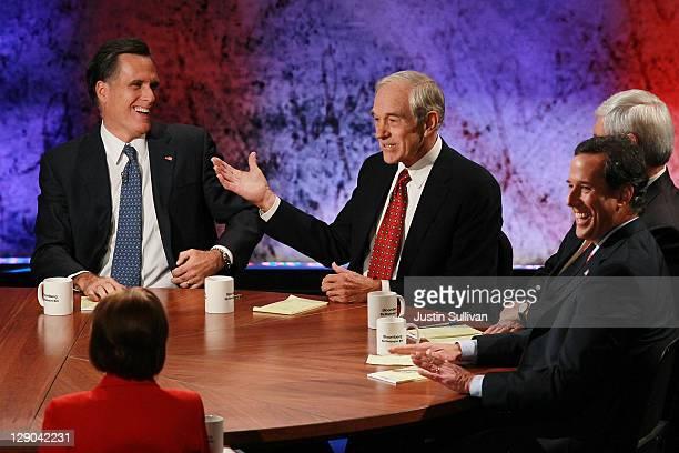 S Rep Ron Paul speaks as former Massachusetts Gov Mitt Romney and former US Sen Rick Santorum look on during the Republican Presidential debate...