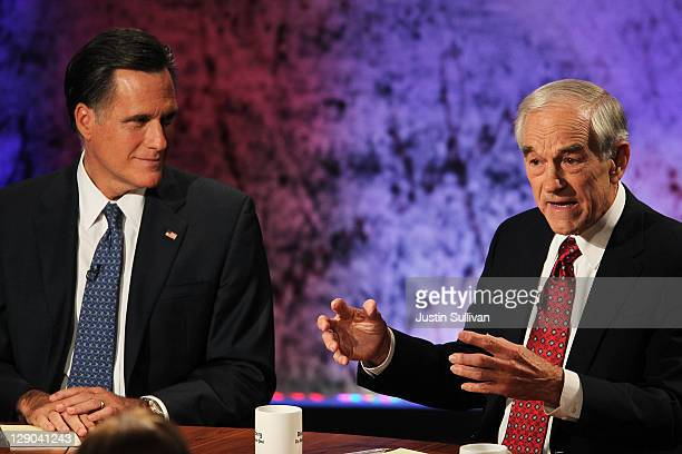 S Rep Ron Paul speaks as former Massachusetts Gov Mitt Romney looks on during the Republican Presidential debate hosted by Bloomberg and the...