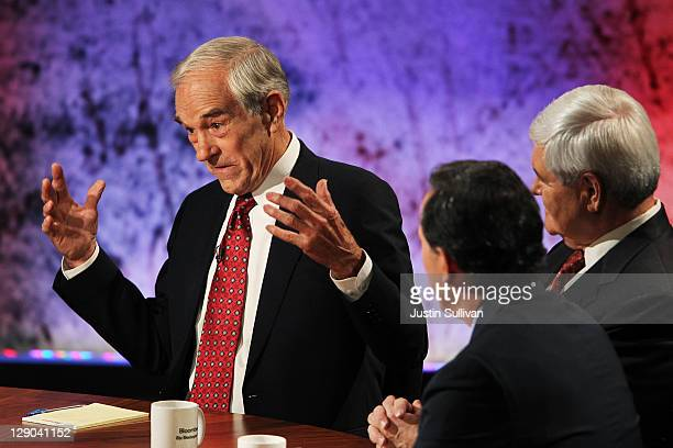S Rep Ron Paul speaks as former Speaker of the House Newt Gingrich and former US Sen Rick Santorum look on during the Republican Presidential debate...