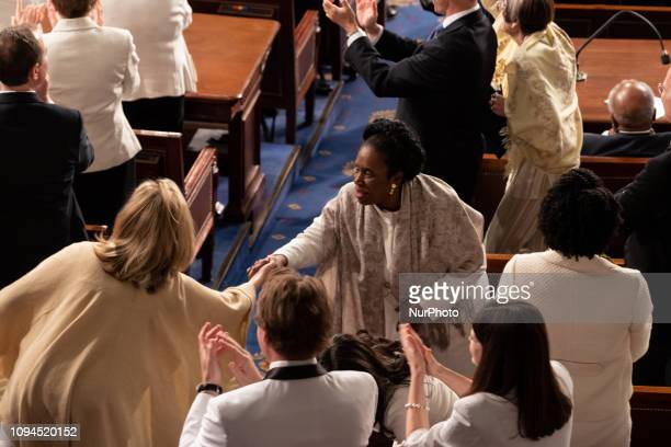 Rep Sheila Jackson Lee shakes hands with a fellow member during US President Donald Trump's second State of the Union address to a joint session of...