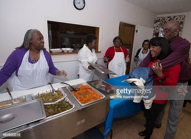 Rep Terri Sewell chats with food servers l to r Sharon Sanders Mary T Jackson Scherrill Jiles and Mattie Coleman as she gets a hug from church member...