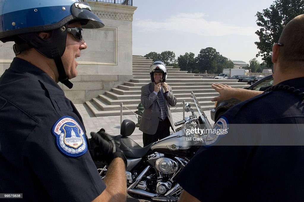 Rep. Tim Walberg, R-Mich., today participated in National Ride to Work Day and rode a Harley Davidson to the east steps of the U.S. Capitol on Wednesday, July 18, 2007. Walberg is flanked by U.S. Capitol Police officers Patrick Collier, left, and Ryan Gainey.