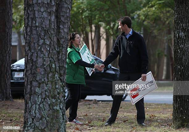 S Rep Tom Cotton and republican candidate for US Senate in Arkansas greets a person who is campaigning outside of a polling place on November 4 2014...