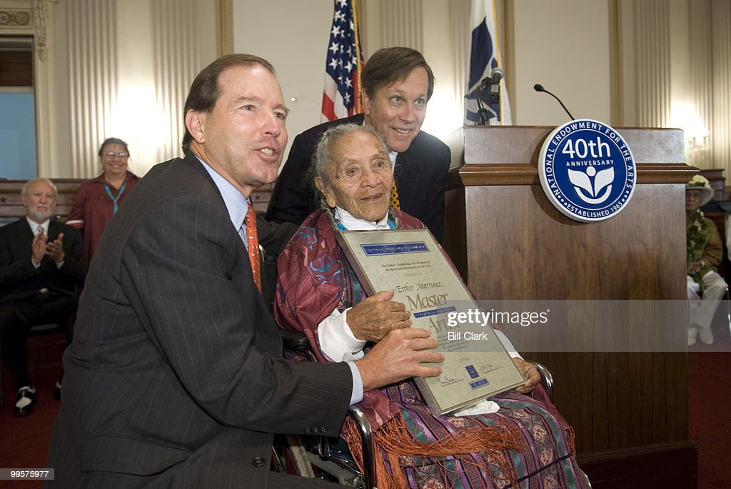 Rep. Tom Udall, D-NM, left, presents storyteller Esther Martinez, of San Juan Pueblo, N.M., with the National Endowment for the Arts' National Heritage Fellowship certificate, with help from NEA chairman Dana Gioia on Thursday, Sept. 14, 2006, in the Cannon Caucus Room. the National Endowment for the Arts annually awards one-time-only NEA National Heritage Fellowships to master folk and traditional artists. These fellowships recognize lifetime achievement, artistic excellence, and contributions to our nation's traditional arts heritage. Eleven fellowships were awarded this year.