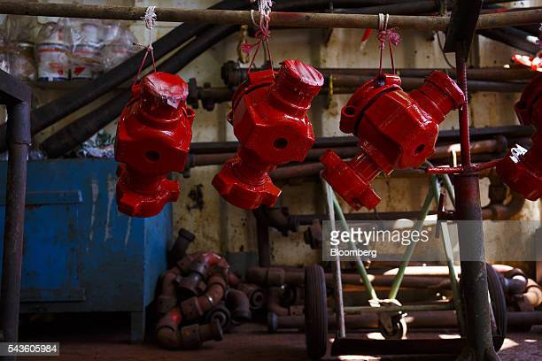 Repainted red valve units hand to dry on pipework on the Casablanca oil platform operated by Repsol SA in the Mediterranean Sea off the coast of...