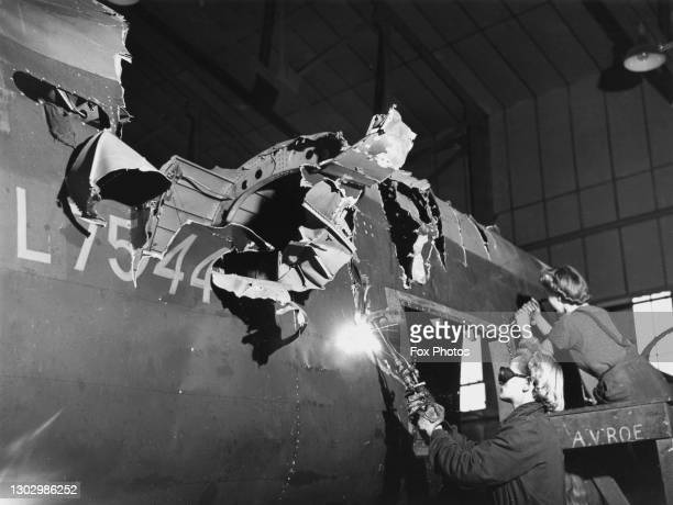Repair and Maintenance Service workers use an oxy-acetylene torch to cut through the rear section of a damaged Avro Lancaster four-engined heavy...