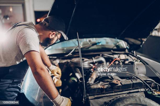 repair man working in garage on repair of old timer - engine stock pictures, royalty-free photos & images