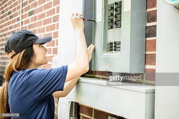 Repair woman, electrician repairing home breaker box.