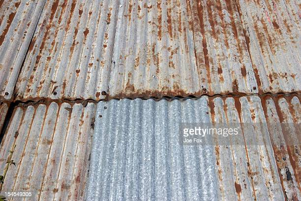 A repaired, weathered corrugated iron sheet roof