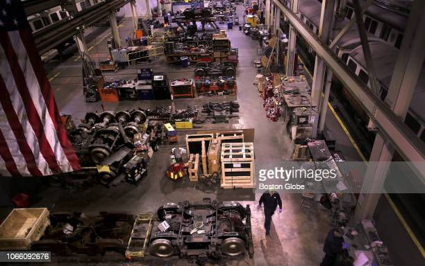 Repairer walks among rail trucks and spare parts in the cavernous facility at Wellington Yard in Medford, MA on Nov. 8, 2018. New Orange Line cars...