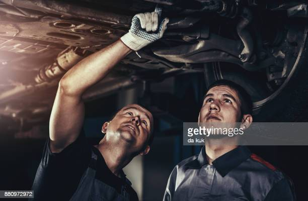 repairing a car in auto repair shop - machine part stock pictures, royalty-free photos & images