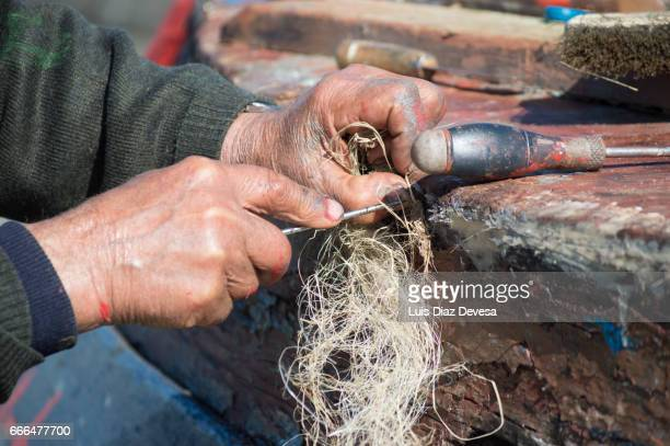 repairing a leak on the boat's hull - un solo hombre stock photos and pictures