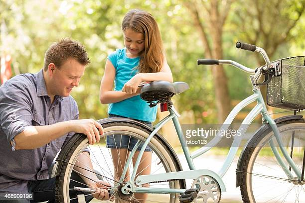 Repairing bike with daddy. Little girl, father outdoors. Yard. Summer.