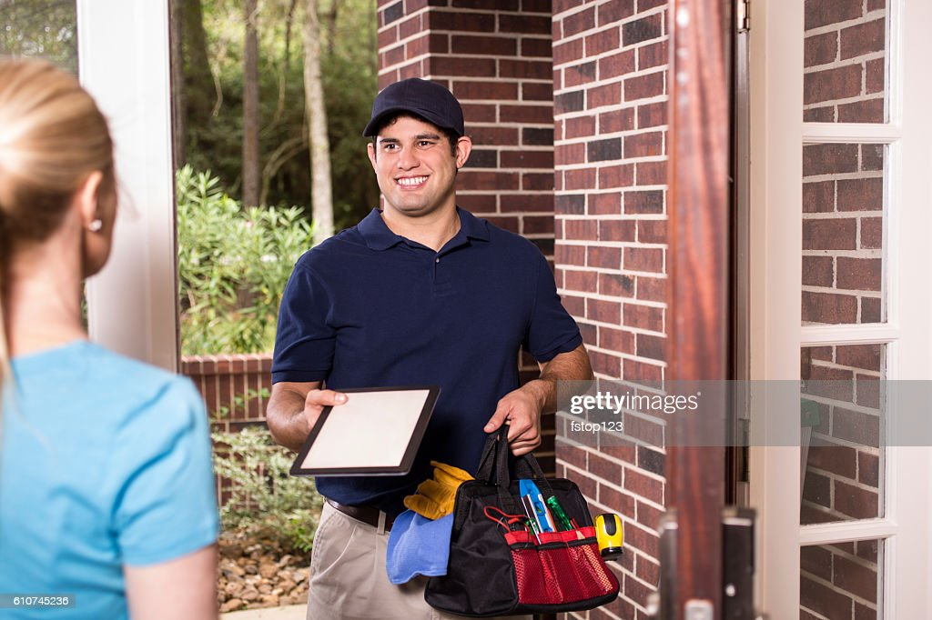 Repairman at customer's front door. : Stock Photo