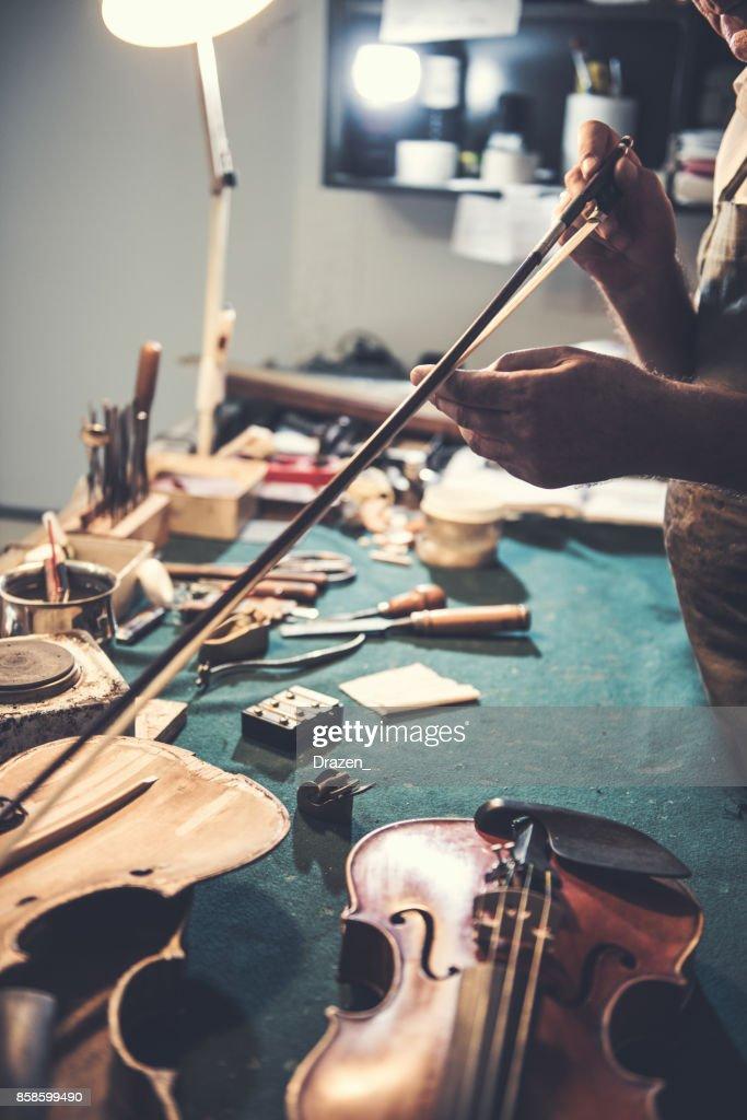 Mechaniker überprüfen die Geige Bogen auf der Geige : Stock-Foto