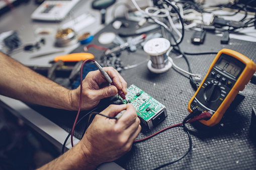 Repairman Checking Voltage With Digital Multimeter 1006169700