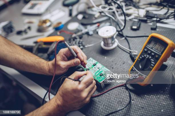 repairman checking voltage with digital multimeter - electricity stock pictures, royalty-free photos & images