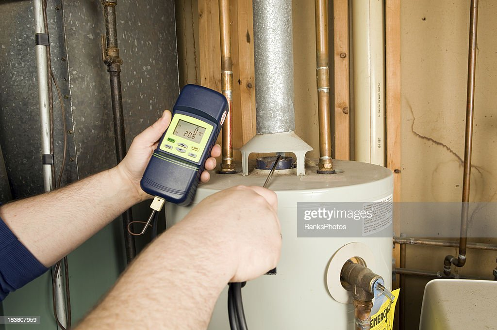 Repairman Checks Carbon Monoxide Level on Gas Water Heater Exhaust : Stock Photo