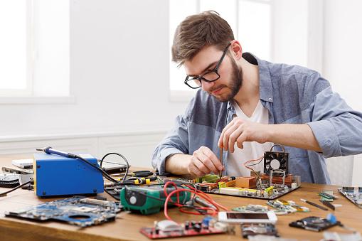 Repairman disassemble motherboard with screwdriver 871927176