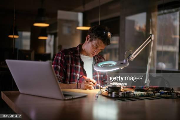 Repairman disassembling laptop motherboard