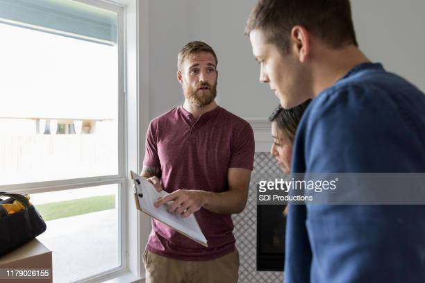 repairman gives repair estimate to young couple - inspector stock pictures, royalty-free photos & images