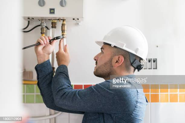 repairman installing a natural gas boiler at a house - repairing stock pictures, royalty-free photos & images
